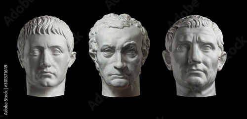 Three gypsum copy of ancient statue heads isolated on a black background Fototapeta
