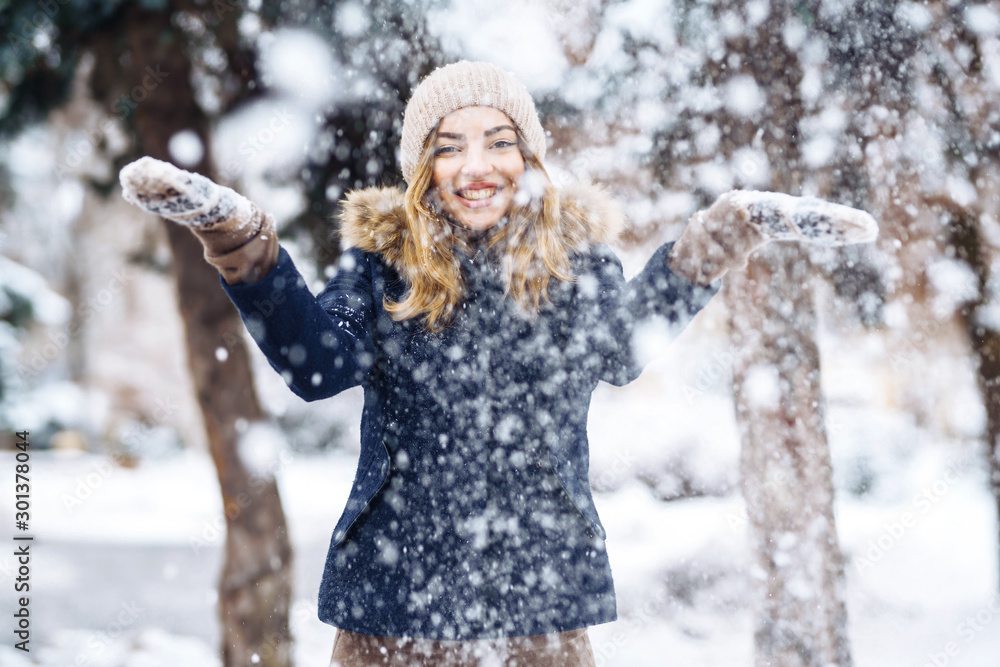 Fototapeta Beautiful girl playing with snow in winter forest. Smiling girl in a blue jacket and knitted hat and mittens having fun with snow falling in hands. Fashion young woman in the winter park. Christmas.