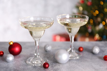 Beautiful Christmas Composition With Two Glasses Of Sparkling Wine, Decorations On Textured Table. New Year's Eve Tradition To Celebrate With Champagne. Close Up, Copy Space, Background.
