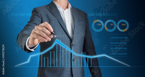 Fototapeta Businessman marks with a pencil on the graph the trend of economic growth obraz na płótnie