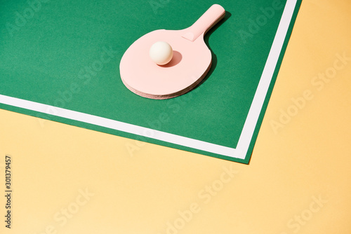 plakat Ping pong ball on racket and playing table on yellow surface