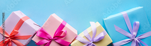 Fotografija top view of colorful gift boxes on blue background, panoramic shot