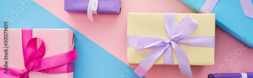 top view of colorful gift boxes with ribbons and bows on blue and pink background, panoramic shot