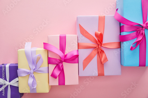 flat lay with colorful gift boxes with ribbons and bows scattered on pink background with copy space