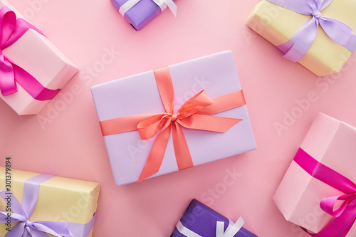 top view of colorful gift boxes with ribbons and bows on pink background