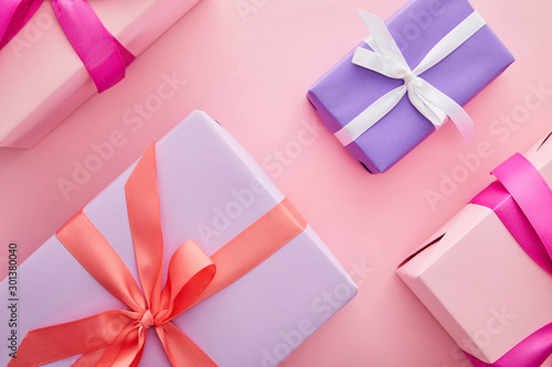 flat lay with colorful gift boxes with ribbons and bows scattered on pink background