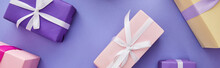 Top View Of Colorful Presents With Bows Scattered On Purple Background, Panoramic Shot