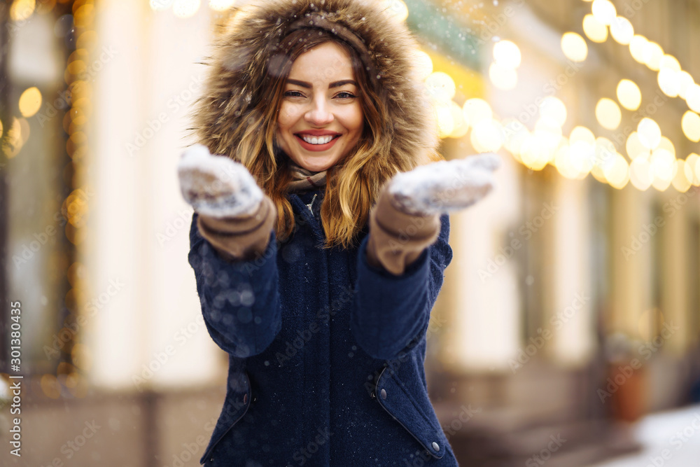 Fototapety, obrazy: Beautiful  girl in a blue jacket and knitted hat and mittens posing in street of city. Garland lights. Enjoying snow, smiling to camera, cheerful  new year mood, true emotions. Winter fashion.