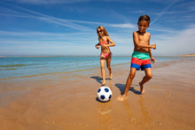 Young Boy And Girl Play Soccer Ball On The Beach