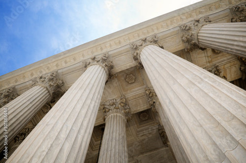 Low angle view of grand classical stone columns soaring up to decorative entabla Wallpaper Mural