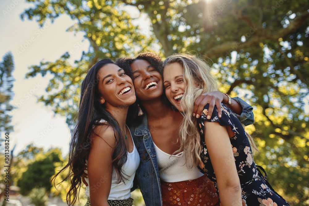 Fototapeta Portrait of a happy multiethnic group of smiling female friends - women laughing and having fun in the park on a sunny day