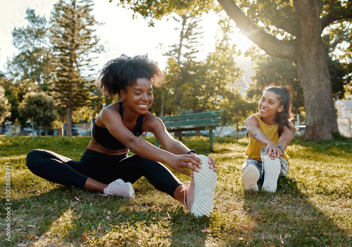 Fototapeta Young diverse female friends sitting on green grass stretching her legs in the morning sunlight at park - diverse friends warming up before doing group exercise  obraz