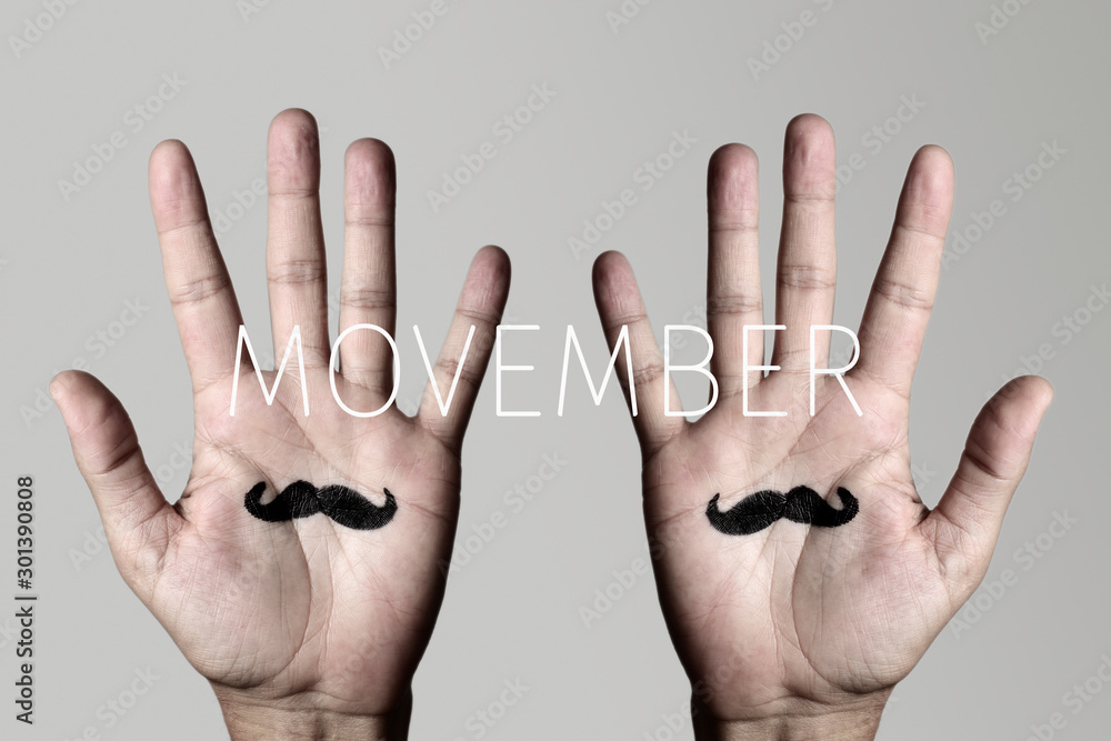 Fototapeta moustache in man hands and text movember