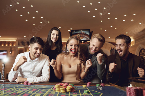 Fotografia Happy people are betting in gambling at roulette poker in a casino