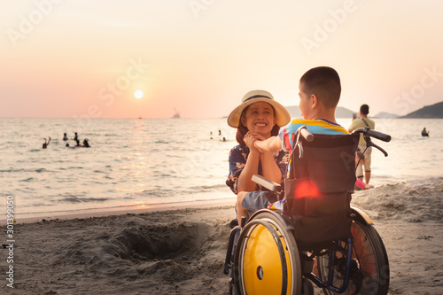 Valokuva  Mother and Asian special child on wheelchair is happily on the beach,Mom and son spend holiday to travel and learning about nature around the sea,Life in the education age, Happy disabled kid concept