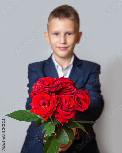 A boy in a blue suit holds a bouquet of red roses. Grey background.