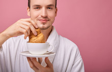 Funny Guy In Snow-white Bathrobe Is Dipping Croissant In Tea