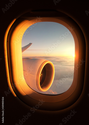Obraz na plátně View out of an airplane window of the jet's wing and engine with a stunning suns