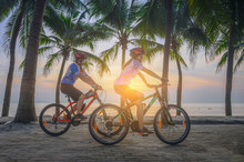 Couple Lover Enjoy Riding Bicycle Under Coconut Palm Trees At Light Of Sunset, Relax And Comfortable At The End Of The Day Together