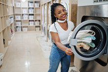 Cheerful African American Woman With Towels In Hands Near Washing Machine In The Self-service Laundry.