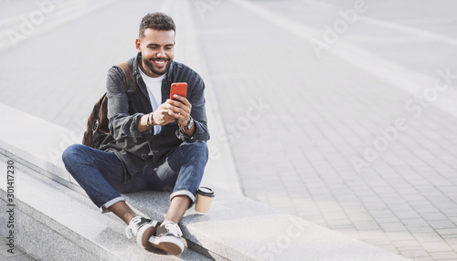 fototapeta na lodówkę Young handsome men using smartphone in a city. Smiling student man texting on his mobile phone. Coffee break. Modern lifestyle, connection, business concept