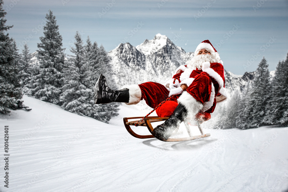 Fototapeta Red Santa Claus riding a wooden sled. An older man with a beard delivers presents to a child. Winter mountains landscape and snow-covered trees with frost. Fir branches, winter time. Christmas spells