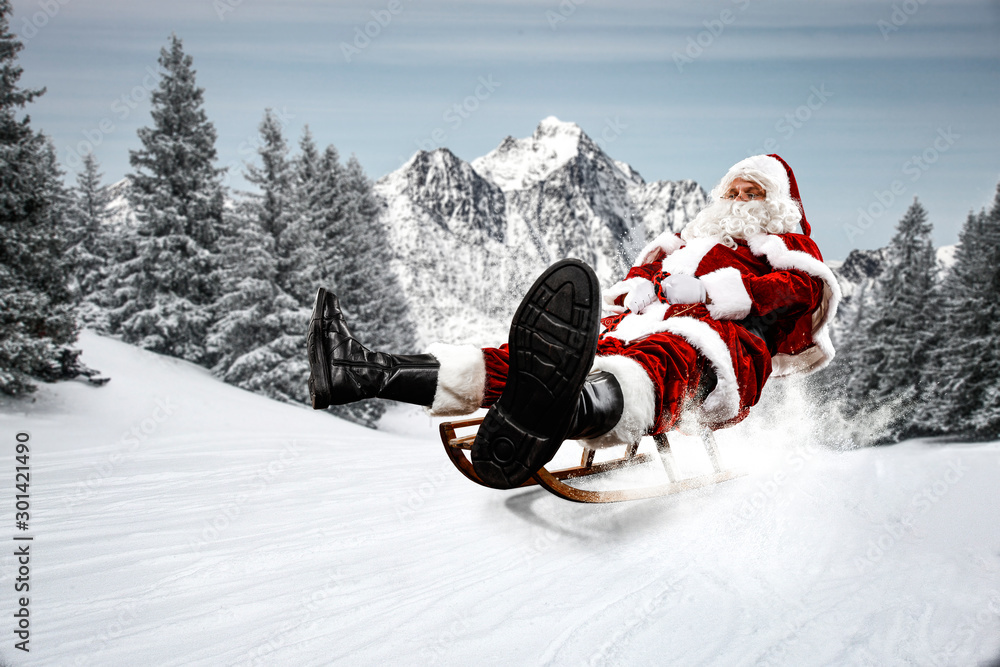 Fototapety, obrazy: Red Santa Claus riding a wooden sled. An older man with a beard delivers presents to a child. Winter mountains landscape and snow-covered trees with frost. Fir branches, winter time. Christmas spells