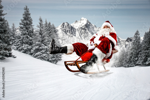 Poster Individuel Red Santa Claus riding a wooden sled. An older man with a beard delivers presents to a child. Winter mountains landscape and snow-covered trees with frost. Fir branches, winter time. Christmas spells