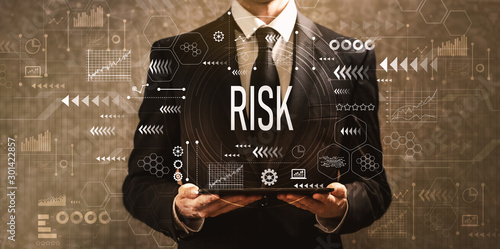 Risk with businessman holding a tablet computer on a dark vintage background Canvas Print