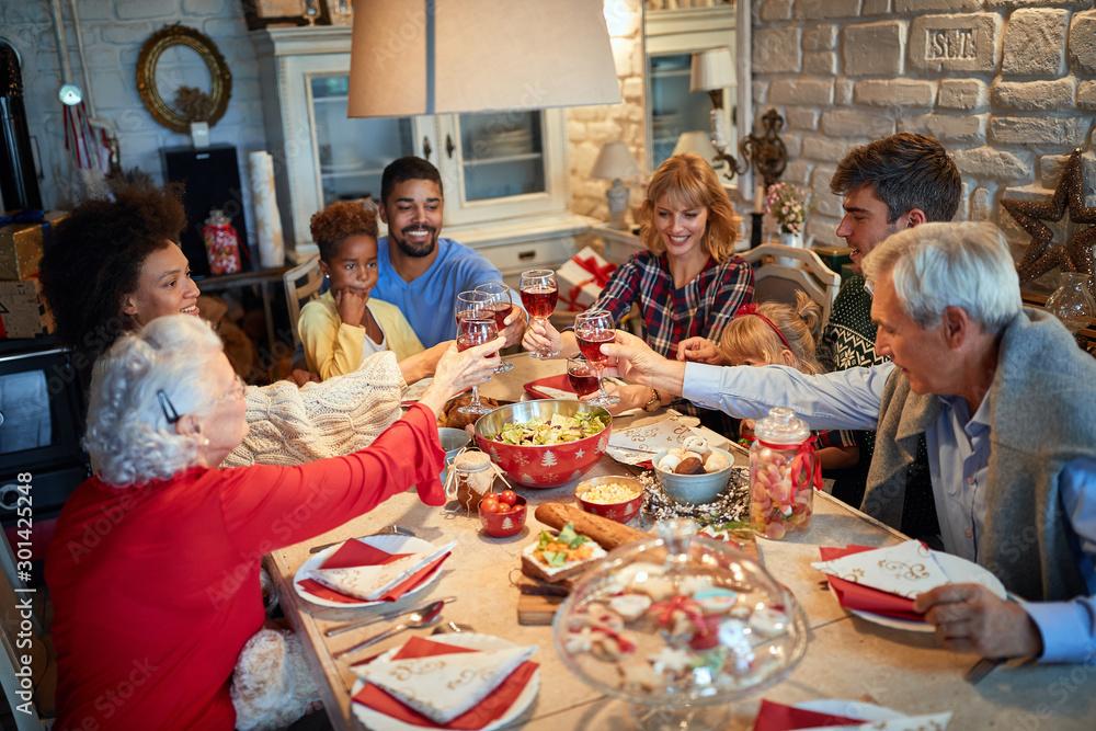 Fototapeta Family having Christmas dinner at home with happy friends