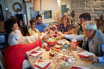 Fototapeta na wymiar Family having Christmas dinner at home with happy friends
