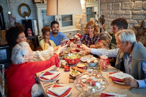 Family having Christmas dinner at home with happy friends - 301425248