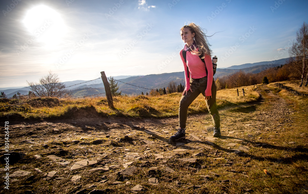 Fototapety, obrazy: Hiker young woman with backpack rises to the mountain top on mountains landscape background