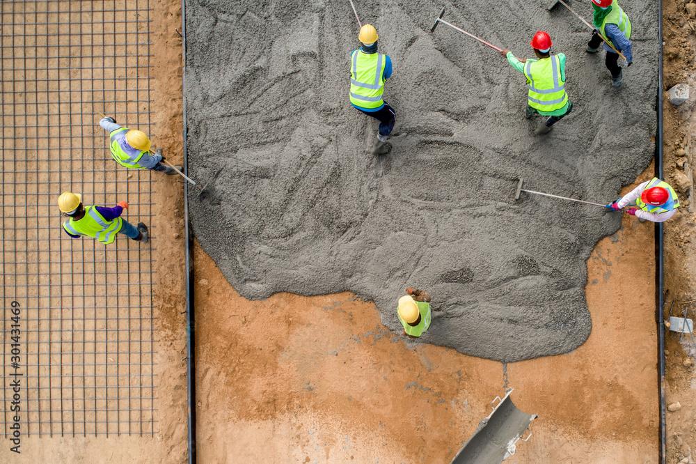 Fototapeta A construction worker pouring a wet concret at road construction site