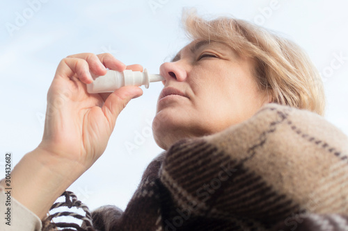 Fotografia, Obraz Sick ill elderly senior mature woman drips, injecting nasal drope for blocked nose