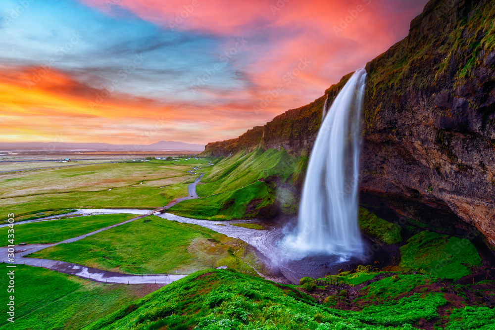 Fototapety, obrazy: Sunrise on Seljalandfoss waterfall on Seljalandsa river, Iceland, Europe. Amazing view from inside. Landscape photography