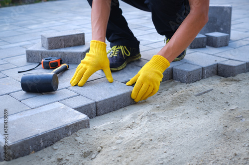 Fototapeta The master in yellow gloves lays paving stones in layers. Garden brick pathway paving by professional paver worker. Laying gray concrete paving slabs in house courtyard on sand foundation base. obraz