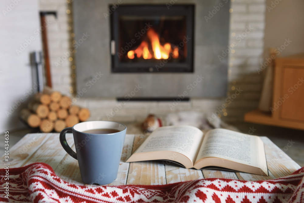 Fototapeta Hygge concept with open book and cup of tea near burning fireplace
