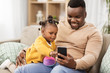Leinwandbild Motiv family, fatherhood and technology concept - african american father with smartphone and little baby daughter playing with ball at home