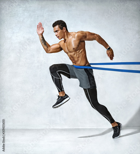 Strong man in silhouette using a resistance band Wallpaper Mural