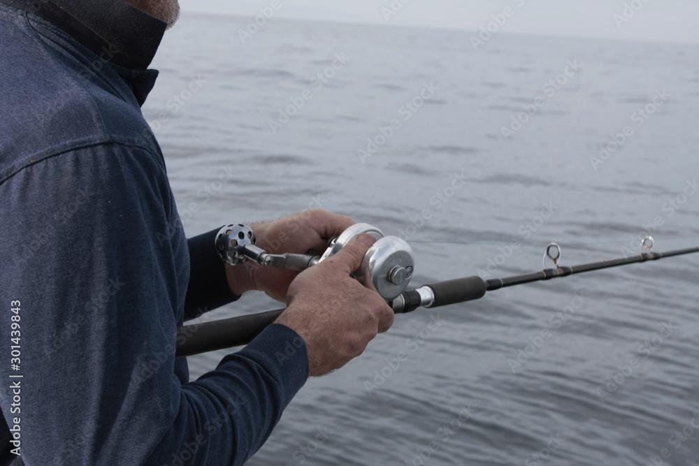 Fototapeta Pescador manejando la caña de pesca