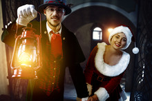 Two Friends Inside. Friends Walking Down The Corridor With A Lighted Lamp. A Young Woman In A Red Dress And Santa's Hat. A Man In A Tuxedo And A Gray Hat With A Red Lamp.