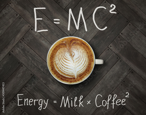 The cup of black energy coffee with milk and two funny formulas. Wooden backg...