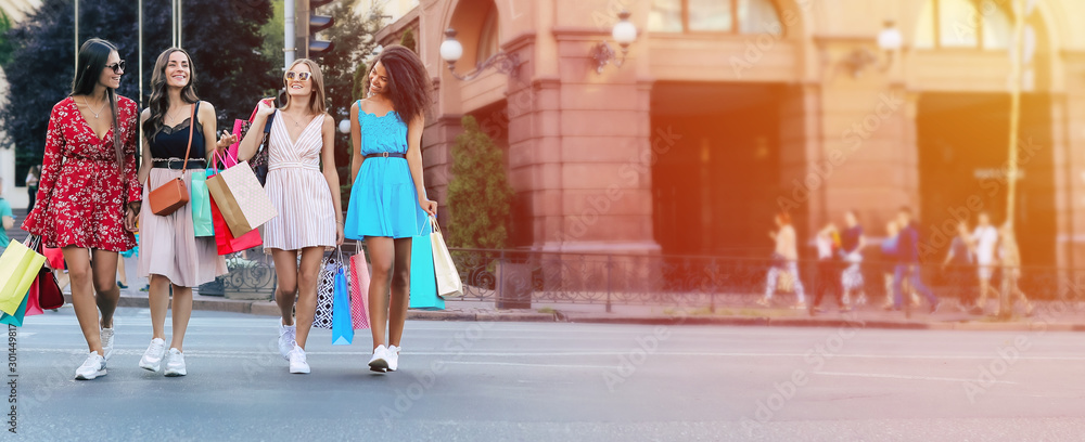 Fototapeta Crossing roads. Full-length photo of four beautiful women walking along the city street in sophisticated dresses and carrying shopping bags, laughing and chatting to each other.