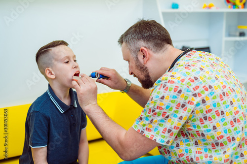Fotografie, Tablou  Professional male doctor checks lymph nodes of a little boy in medical center