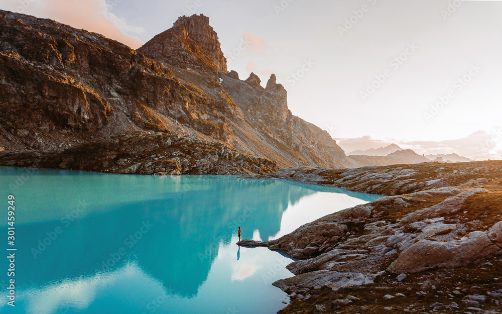 Fototapety, obrazy: Adventurous man standing on cliff overlooking beautiful Swiss Rockies and Wildsee Lake during a vibrant Autumn sunset. Taken in the Swiss Alps, Switzerland, Europe