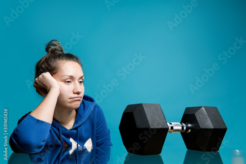 Fototapeta the girl looks in frustration and longing at the big dumbbell lying in front of