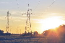 Steel Power Lines On A Rural Field In The Evening At Sunset