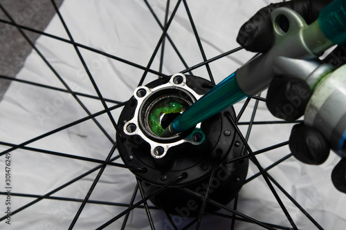 Close up photo of a bicycle mechanic's hand wearing a black latex glove greasing a bicycle rear hub.  - 301476249
