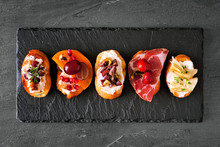 Mixed Crostini Appetizers With A Variety Of Toppings. Top View On A Dark Slate Background. Party Food Concept.